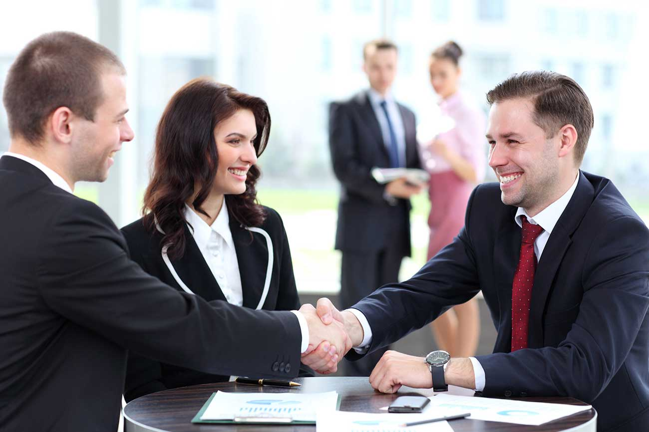 22475294-business-people-shaking-hands-finishing-up-a-meeting
