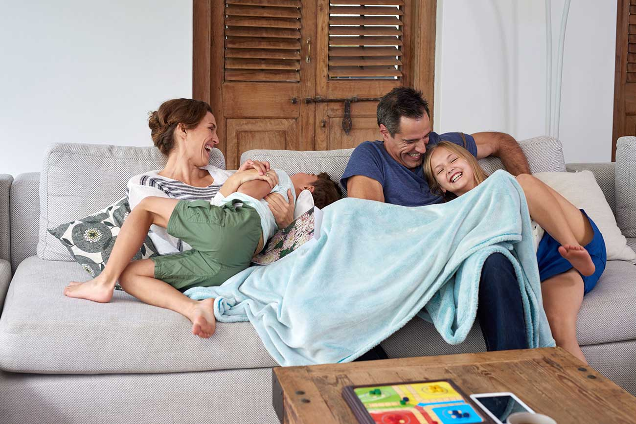 49226040-happy-excited-kids-brother-and-sister-jumping-and-playing-with-parents-on-the-couch-in-living-room
