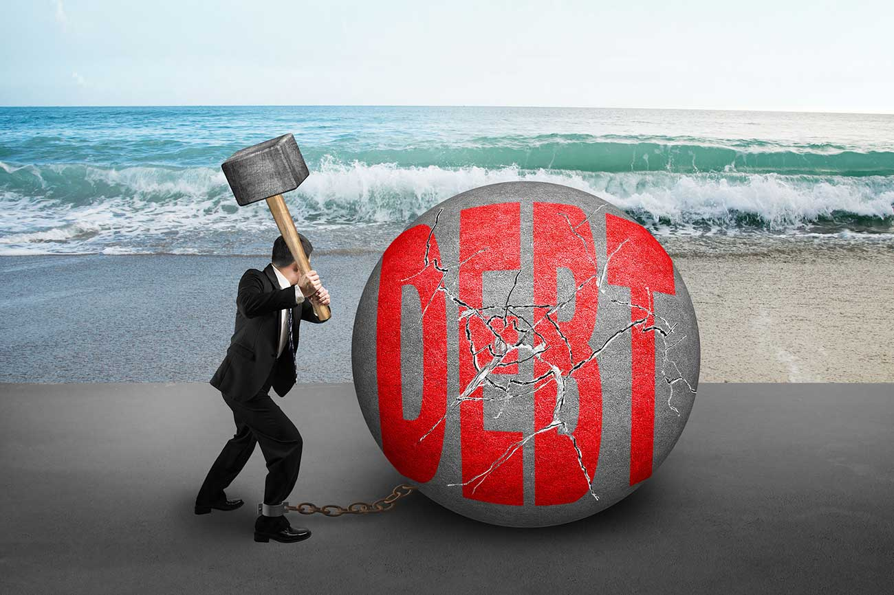 businessman holding hammer hitting cracked DEBT ball with sea beach